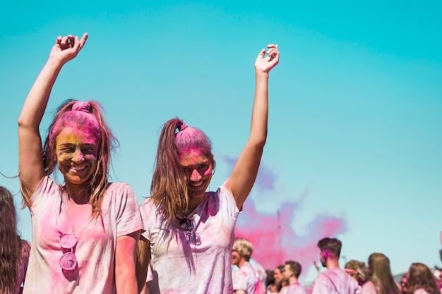 Zwei junge frauen bedeckt mit holi farbtanzen im holi festival Kostenlose Fotos