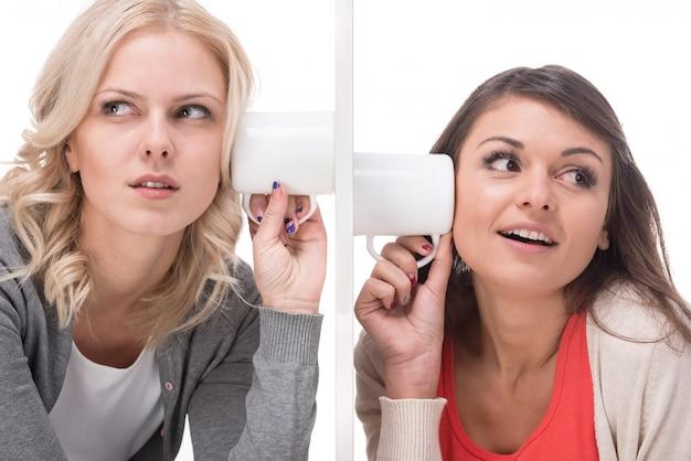 Zwei junge frauen benutzen einen becher, um sich zuzuhören. Premium Fotos