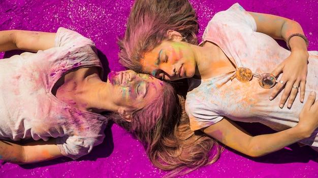 Zwei junge frauen, die auf rosa holi farbpulver liegen Kostenlose Fotos