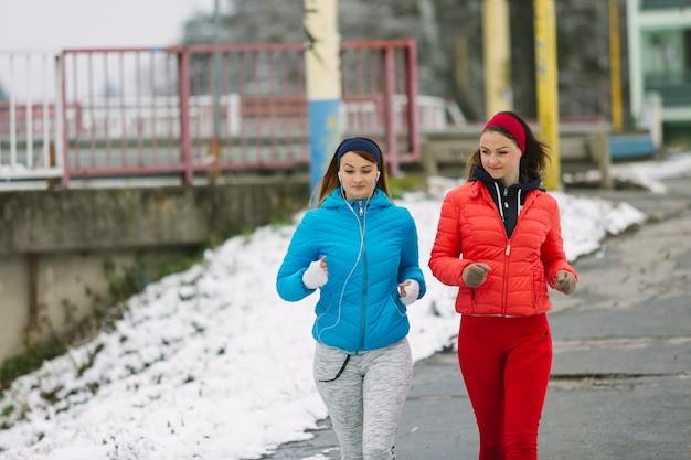 Zwei junge frauen, die auf straße im winter laufen Kostenlose Fotos