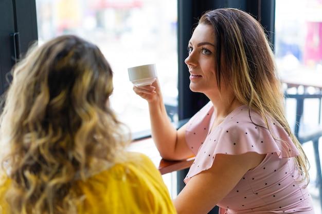 Zwei junge frauen, die kaffee im café trinken Kostenlose Fotos