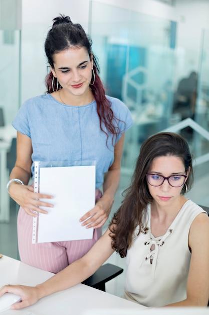 Zwei junge frauen, die mitteilungen auf bildschirm, in einem coworkingraum aufpassen Premium Fotos