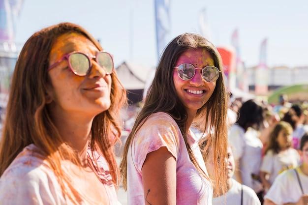 Zwei junge frauen, die sonnenbrille mit holi puder auf gesicht tragen Kostenlose Fotos