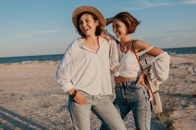 Zwei junge frauen, die spaß am sonnenuntergangsstrand haben, schwule lesbische liebesromantik Kostenlose Fotos
