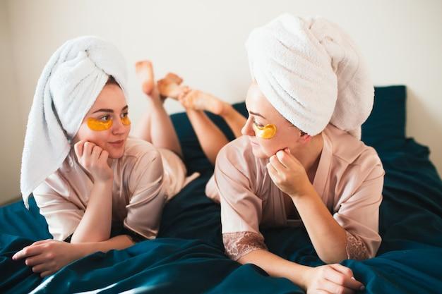 Zwei junge frauen, die spaß mit flecken unter ihren augen haben. zwei freunde in handtüchern und pyjamas veranstalten zu hause gemeinsam eine lustige spa-party. Premium Fotos