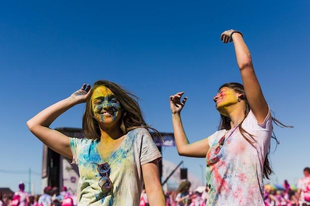 Zwei junge frauen, die während des holi festivals tanzen Kostenlose Fotos