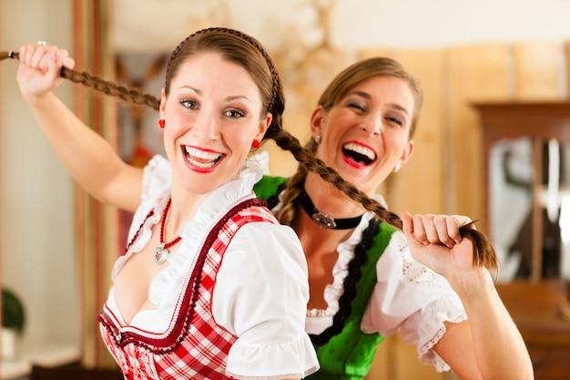 Zwei junge frauen in der traditionellen bayerischen tracht im restaurant oder in der kneipe Premium Fotos