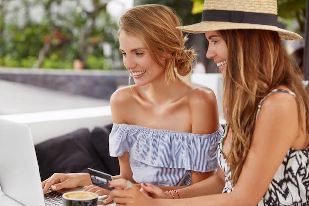 Zwei junge frauen sitzen zusammen in der cafeteria im freien, nutzen einen modernen tragbaren laptop, um online mit kreditkartenzahlung einzukaufen, sehen fröhlich aus, bestellen einen neukauf und surfen im internet Kostenlose Fotos