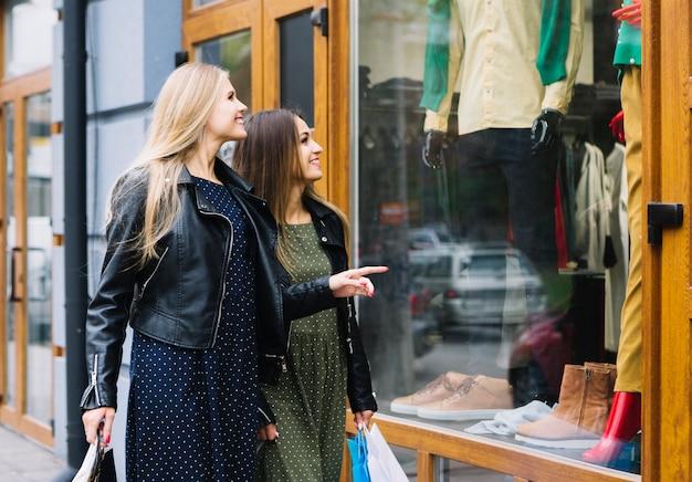 Zwei junge frauen, welche die kleidung im shopfenster betrachten Kostenlose Fotos