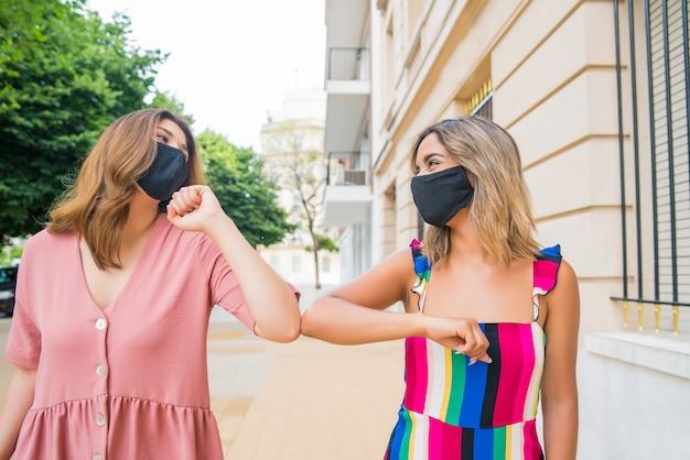 Zwei junge freunde, die gesichtsmaske tragen und ellbogen stoßen, um im freien hallo zu sagen Premium Fotos