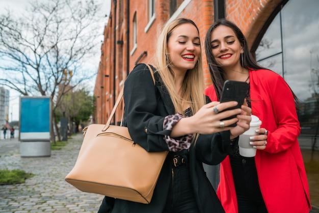 Zwei junge freunde, die ihr handy im freien benutzen. Kostenlose Fotos