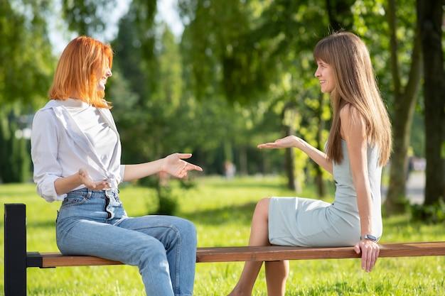 Zwei junge freundinnen sitzen auf einer bank im sommerpark und sprechen mit einem streit. Premium Fotos