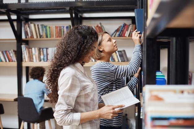 Zwei junge fröhliche studentinnen in freizeitkleidung, die in der nähe von bücherregalen in der universitätsbibliothek stehen und literatur für teamprojekt durchsehen Kostenlose Fotos