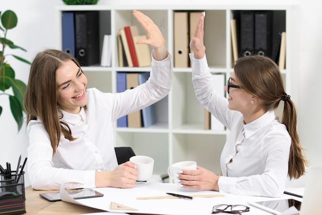 Zwei junge geschäftsfrauen, die einander betrachten, die hoch fünf im büro gibt Kostenlose Fotos