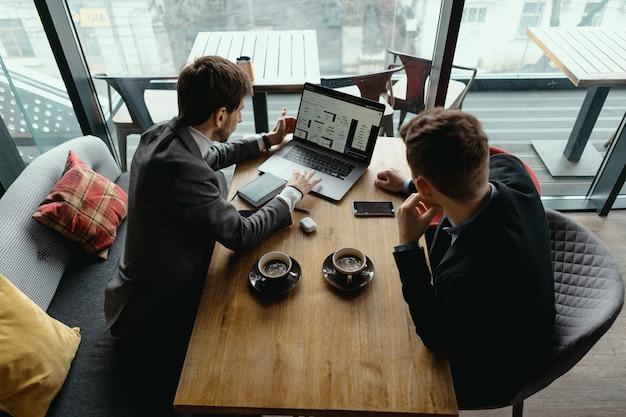 Zwei junge geschäftsleute, die ein erfolgreiches treffen im restaurant haben. Kostenlose Fotos