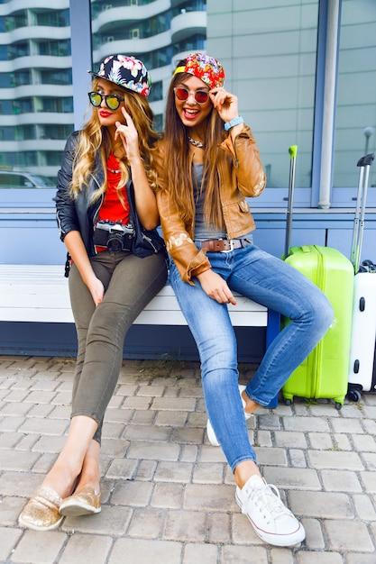 Zwei junge hübsche mädchen, die vor ihren reiseabenteuern die karte erkunden und betrachten, lächeln und spaß vor neuen emotionen haben. bester freund posiert mit seinem gepäck. Kostenlose Fotos