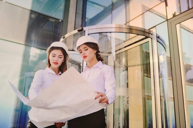Zwei junge hübsche wirtschaftsingenieure der geschäftsfrauen in den bausturzhelmen mit einer tablette in den händen auf einem glasgebäudehintergrund Premium Fotos