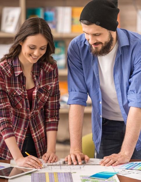 Zwei junge kreative designer, die zusammen an projekt arbeiten. Premium Fotos