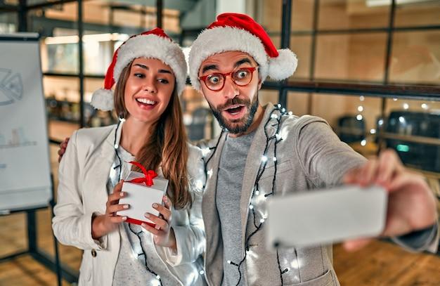Zwei junge kreative menschen in weihnachtsmützen tauschen geschenke aus und machen an ihrem letzten arbeitstag smartphone-selfies. Premium Fotos