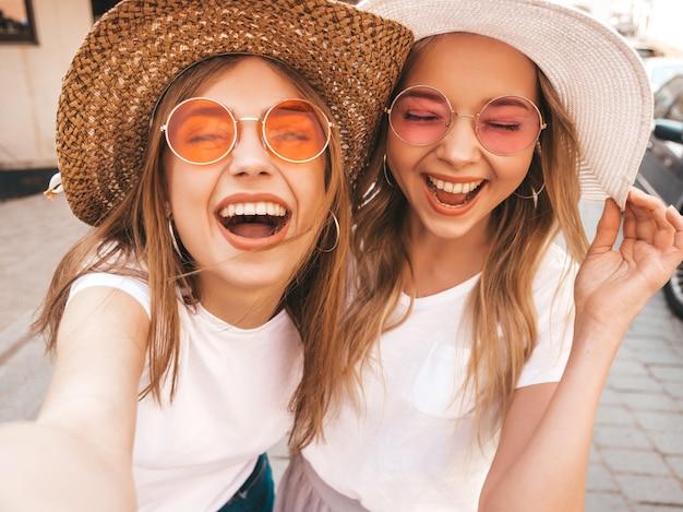 Zwei junge lächelnde blonde frauen des hippies im sommerweißt-shirt. mädchen, die selfie selbstporträtfotos auf smartphone machen modelle, die auf straßenhintergrund aufwerfen frau zeigt zunge und positive gefühle Kostenlose Fotos