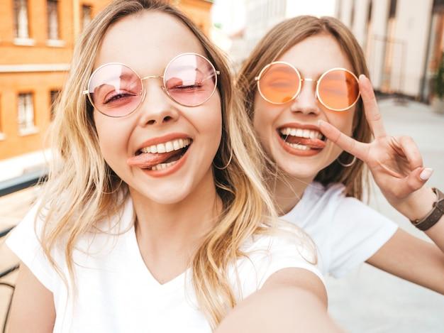 Zwei junge lächelnde blonde frauen des hippies im weißen t-shirt des sommers kleidet. mädchen, die selfie selbstporträtfotos auf smartphone machen. frau zeigt friedenszeichen und -zunge Kostenlose Fotos