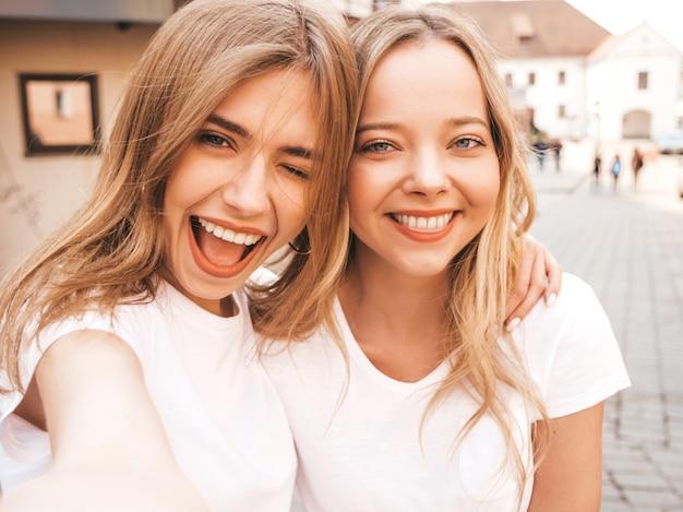 Zwei junge lächelnde blonde frauen des hippies im weißen t-shirt des sommers kleidet. mädchen, die selfie selbstporträtfotos auf smartphone machen. Kostenlose Fotos