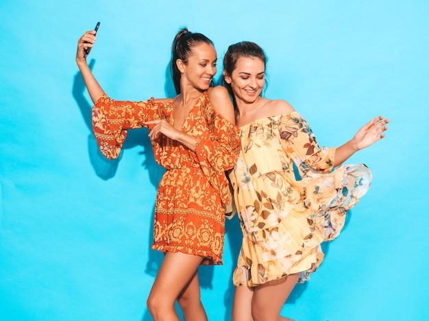 Zwei junge lächelnde hippie-frauen in den sommerhippie-fliegenkleidern mädchen, die selfie selbstporträtfotos auf smartphone machen modelle, die nahe blauer wand im studio aufwerfen frauen, die positive gesichtsgefühle zeigen Kostenlose Fotos