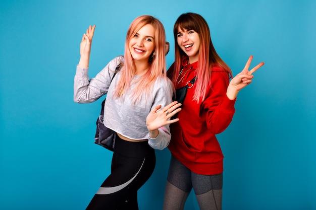 Zwei junge lustige hübsche hipster-frauen, die sportliche helle lässige outfits tragen, schreiend lächeln und hallo zu ihnen sagen, blaue wand Kostenlose Fotos
