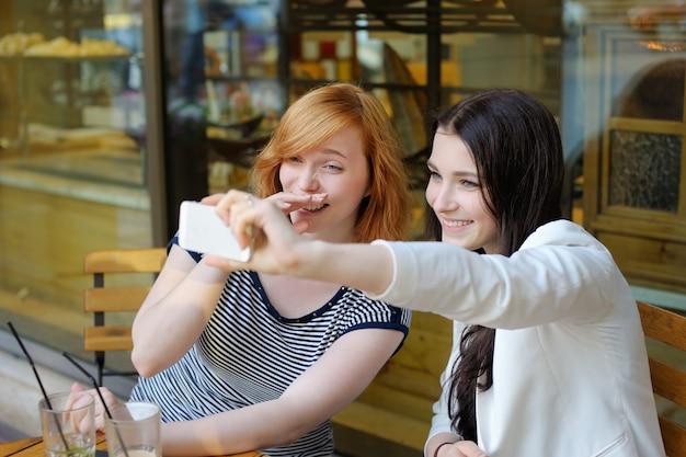 Zwei junge mädchen, die ein selbstporträt (selfie) mit intelligentem telefon nehmen Premium Fotos