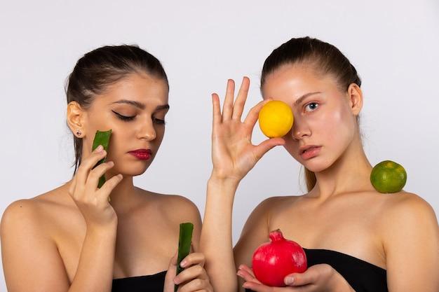 Zwei junge mädchen, eine braunhaarige frau mit früchten in der hand, eine brünette mit aloe vero. auf weiß isoliert. spa und gesundes lebensmittelkonzept. hochwertiges foto Premium Fotos