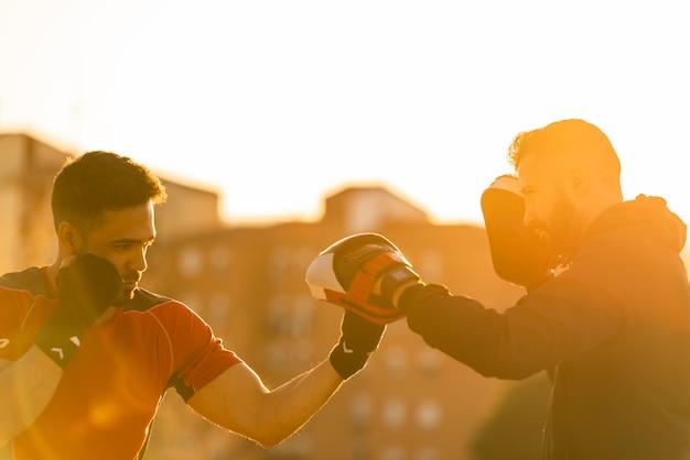 Zwei junge männer, die draußen boxen. Premium Fotos