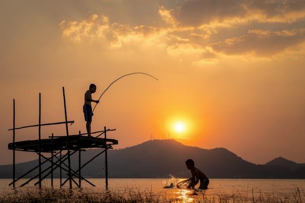 Zwei junge nette jungen, die an einem see an einem sonnigen sommertag fischen. Premium Fotos