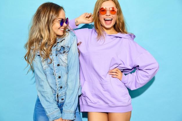 Zwei junge schöne blonde lächelnde hippie-frauen im modischen sommer kleidet. sexy sorglose frauen, die nahe blauer wand in der sonnenbrille aufwerfen. positive models werden verrückt Kostenlose Fotos