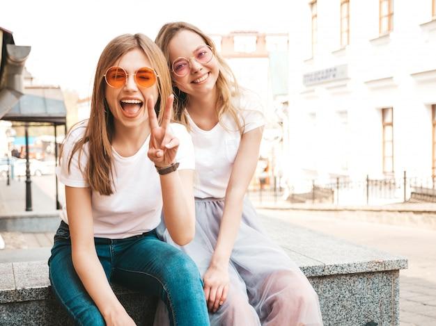Zwei junge schöne blonde lächelnde hippie-mädchen im weißen t-shirt des modischen sommers kleidet. frauen sitzen auf der straße. positive modelle, die spaß in der sonnenbrille haben. zeigt friedenszeichen Kostenlose Fotos