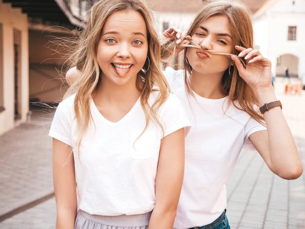 Zwei junge schöne blonde lächelnde hippie-mädchen im weißen t-shirt des modischen sommers kleidet. positive modelle, die spaß haben. schnurrbart mit dem haar machen und zunge zeigen Kostenlose Fotos