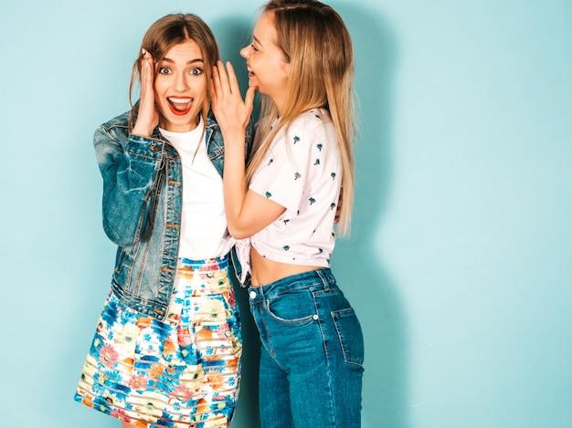 Zwei junge schöne blonde lächelnde hippie-mädchen in der zufälligen kleidung des modischen sommers. Kostenlose Fotos