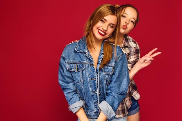 Zwei junge schöne blonde lächelnde hipster-frauen, die in den trendigen sommerlichen karierten hemdkleidern aufwerfen Kostenlose Fotos