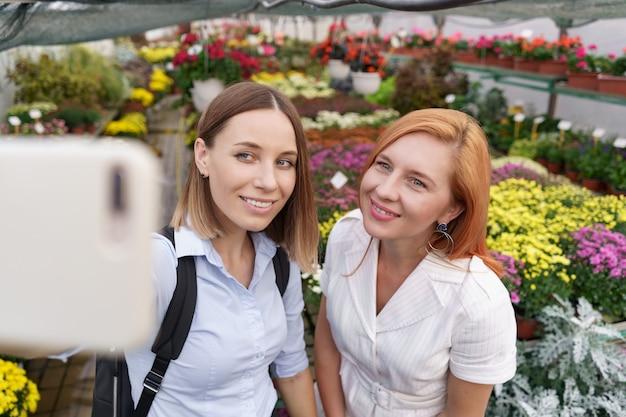 Zwei junge schöne damen machen selfie auf blumenhintergrund im gewächshaus Kostenlose Fotos