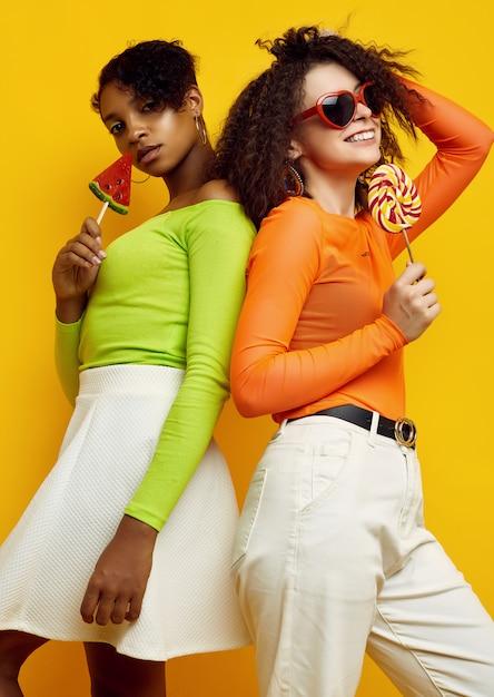 Zwei junge schöne frauen in der bunten sommerkleidung mit lutschern Premium Fotos
