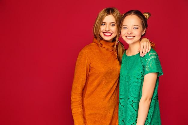Zwei junge schöne frauen posieren in trendigen kleidern Kostenlose Fotos