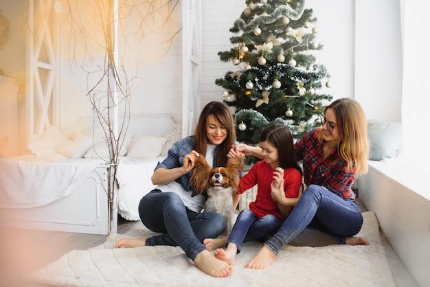 Zwei junge schöne frauen und kleines mädchen, während weihnachten zu hause feiern Premium Fotos