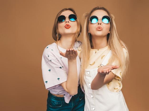 Zwei junge schöne lächelnde blonde hippie-mädchen im bunten t-shirt des modischen sommers kleidet. sexy sorglose frauen, die nahe beige wand in der runden sonnenbrille aufwerfen. positive modelle, die luftkuss geben Kostenlose Fotos