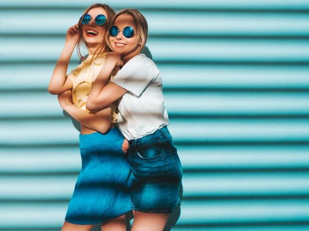 Zwei junge schöne lächelnde blonde hippie-mädchen im bunten t-shirt des modischen sommers kleidet. Kostenlose Fotos