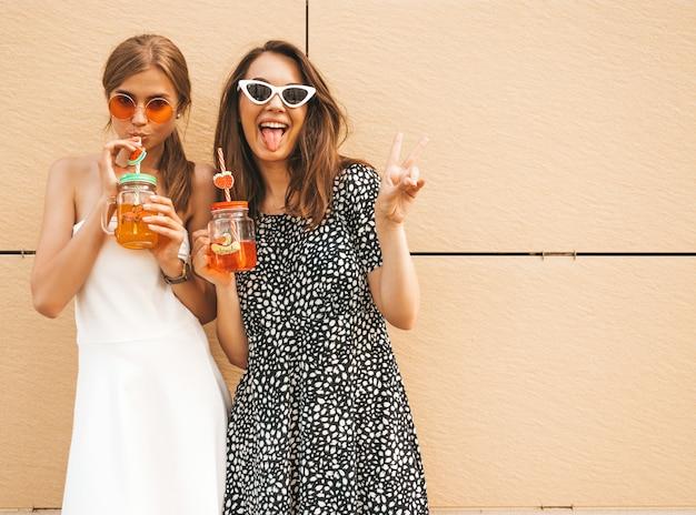 Zwei junge schöne lächelnde hippie-mädchen in den modischen sommerkleidern. Kostenlose Fotos