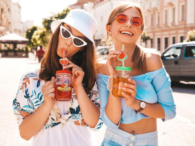 Zwei junge schöne lächelnde hippie-mädchen in der modischen sommerkleidung und im panama-hut. Kostenlose Fotos