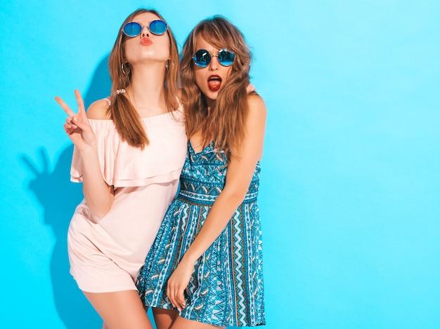 Zwei junge schöne lächelnde mädchen in den modischen sommerkleidern und -sonnenbrille. sexy sorglose frauenaufstellung. positive vorbilder Kostenlose Fotos