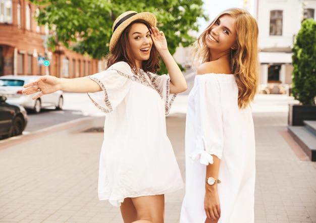 Zwei junge stilvolle hippie-brünette und blonde frauenmodelle ohne make-up im sonnigen sommertag in der weißen hipster-kleidung, die aufwirft. dreh dich um und bitte, mit ihnen zu gehen Kostenlose Fotos