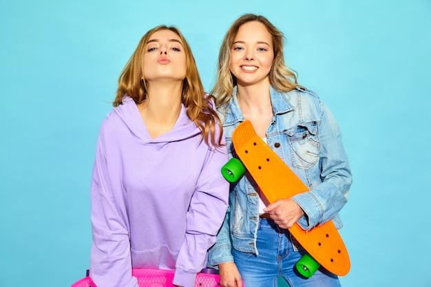 Zwei junge stilvolle lächelnde blonde frauen mit penny-skateboards. frauen in der sommerhippie-sportkleidung, die nahe blauer wand aufwirft. positive vorbilder Kostenlose Fotos