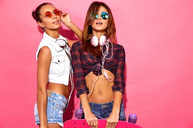 Zwei junge stilvolle lächelnde brunettefrauen mit pennyskateboards. modelle im sommerhippie kleidet die aufstellung nahe rosa wand im studio in der sonnenbrille mit kopfhörern Kostenlose Fotos