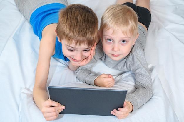 Zwei jungen liegen im bett und betrachten die tablette. freizeitgeräte Premium Fotos